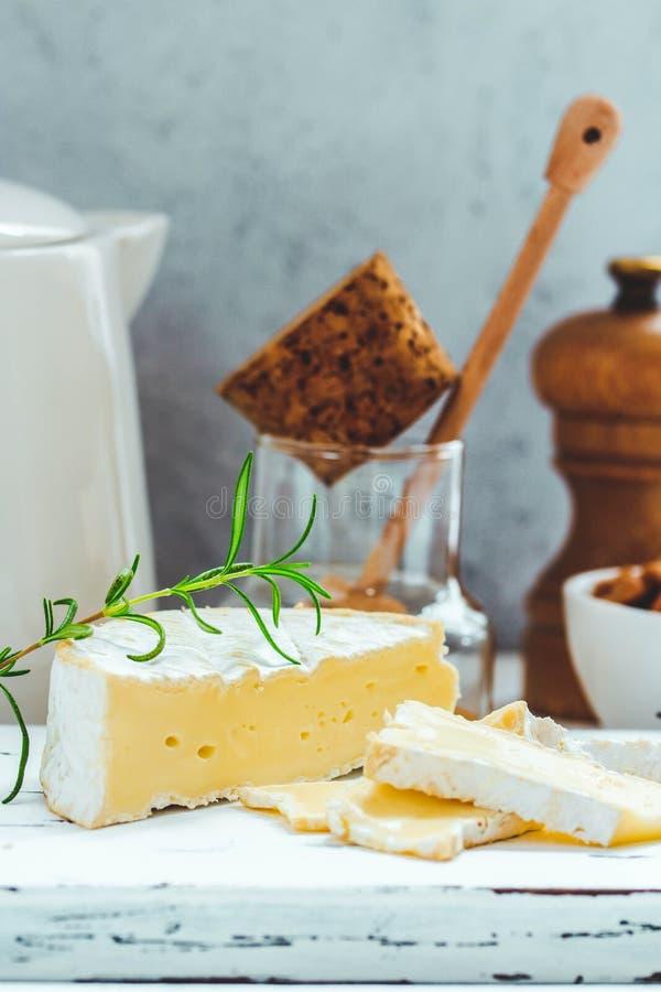 Плита сыра служила с шутихами, медом и гайками Камамбер на белой деревянной доске сервировки над белой предпосылкой текстуры стоковые изображения rf