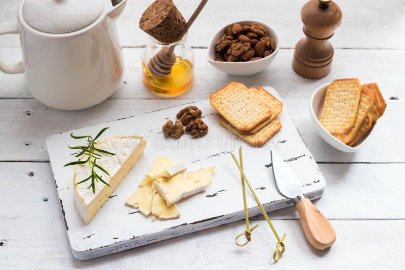 Плита сыра служила с шутихами, медом и гайками Камамбер на белой деревянной доске сервировки над белой предпосылкой текстуры аппе стоковые фотографии rf