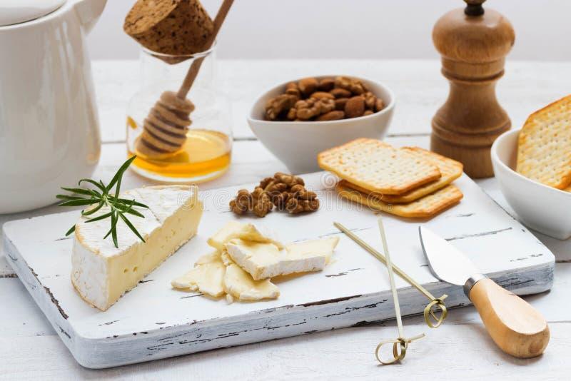 Плита сыра служила с шутихами, медом и гайками Камамбер на белой деревянной доске сервировки над белой предпосылкой текстуры аппе стоковая фотография