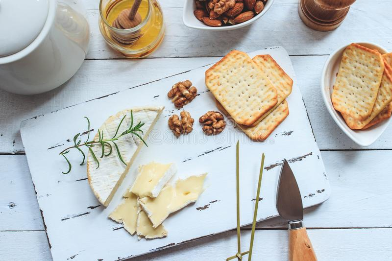 Плита сыра служила с шутихами, медом и гайками Камамбер на белой деревянной доске сервировки над белой предпосылкой текстуры аппе стоковое изображение rf