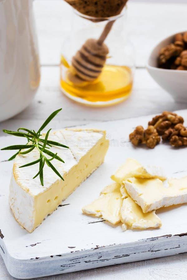Плита сыра служила с шутихами, медом и гайками Камамбер на белой деревянной доске сервировки над белой предпосылкой текстуры аппе стоковое изображение