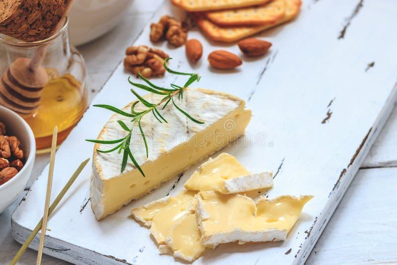Плита сыра служила с шутихами, медом и гайками Камамбер на белой деревянной доске сервировки над белой предпосылкой текстуры аппе стоковые изображения