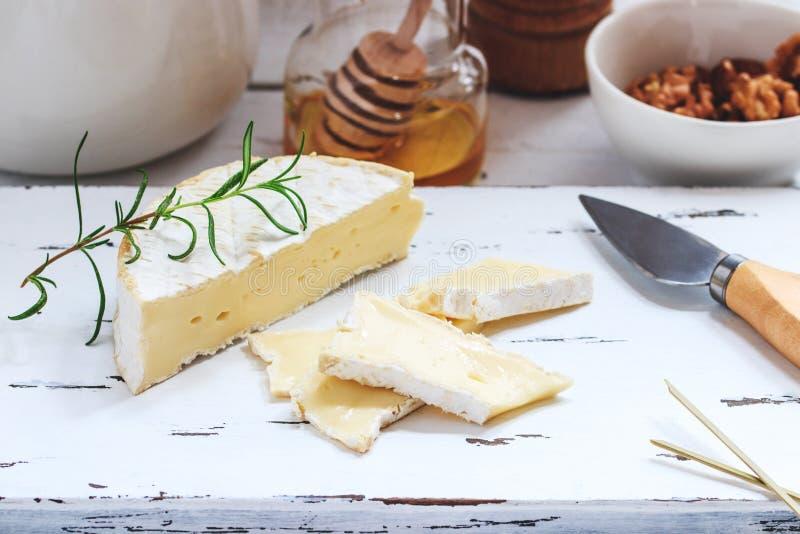 Плита сыра служила с шутихами, медом и гайками Камамбер на белой деревянной доске сервировки над белой предпосылкой текстуры аппе стоковое фото rf