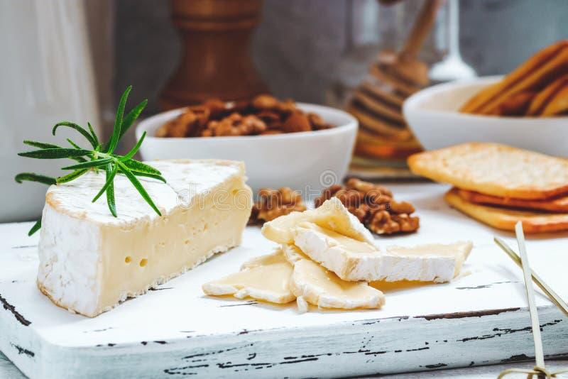 Плита сыра служила с шутихами, медом и гайками Камамбер на белой деревянной доске сервировки над белой предпосылкой текстуры аппе стоковые фото
