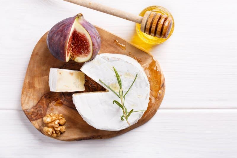 Плита сыра с бри, смоквами, медом и гайками на белой таблице стоковые фото
