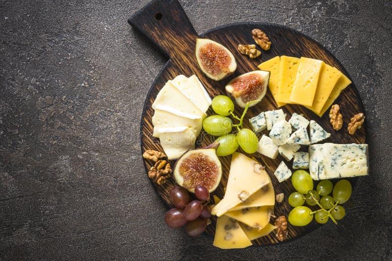Плита сыра с виноградинами, смоквами и гайками стоковое фото