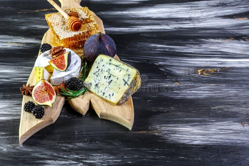 Плита сыра с голубым сыром, бри, сыром трюфеля трудным с виноградинами, смоквами, медом, плодами и гайками r r стоковое изображение