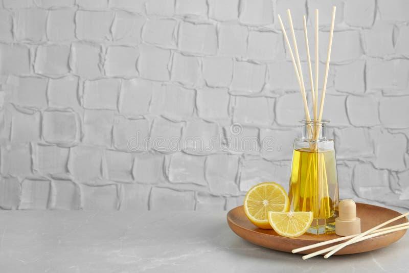 Плита с ароматичным камышовым freshener и лимон на таблице против текстурированной стены стоковые изображения rf