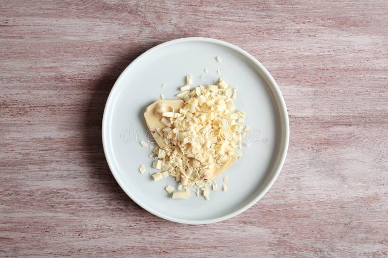 Плита с белыми скручиваемостями шоколада на деревянной предпосылке стоковое фото rf