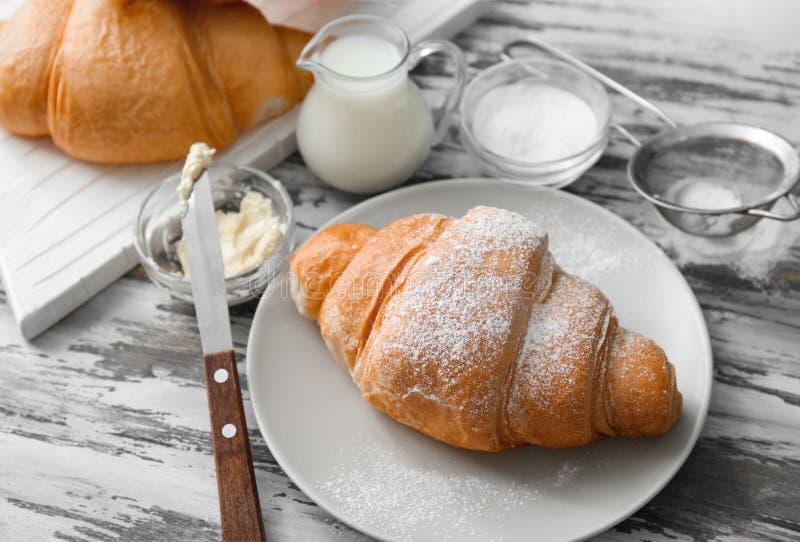 Плита с вкусными круассанами, маслом и молоком на деревянной предпосылке стоковая фотография