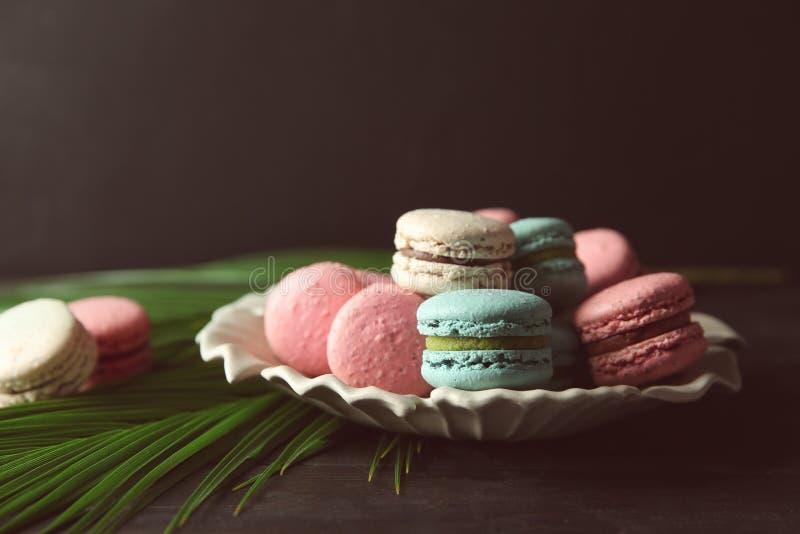 Плита с вкусными macarons и листьями ладони на таблице стоковые фотографии rf