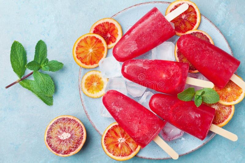 Плита с домодельным мороженым цитруса или popsicles украсили листья мяты и оранжевые куски на взгляде столешницы замороженный фру стоковое фото rf
