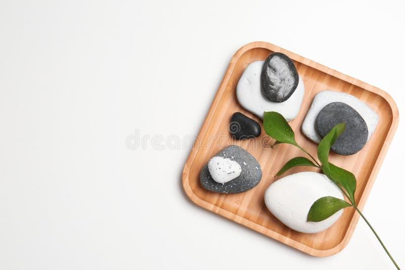 Плита с камнями спа и космос для текста на белой предпосылке стоковое фото
