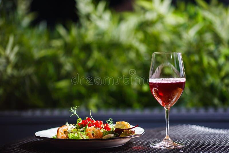 Плита с красивым аппетитным салатом свежих овощей, креветок, яичек триперсток и lingonberries на таблице с питьем стоковое фото rf