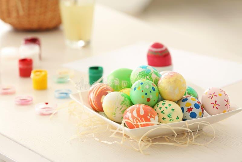 Плита с красочными покрашенными пасхальными яйцами на таблице стоковая фотография