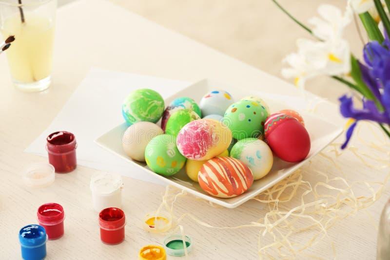 Плита с красочными покрашенными пасхальными яйцами на таблице стоковое фото