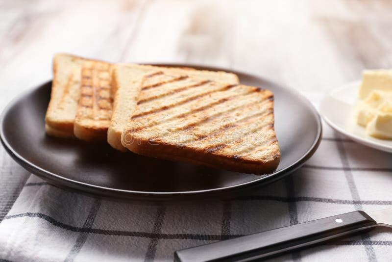 Плита с провозглашанным тост хлебом на таблице стоковые фото