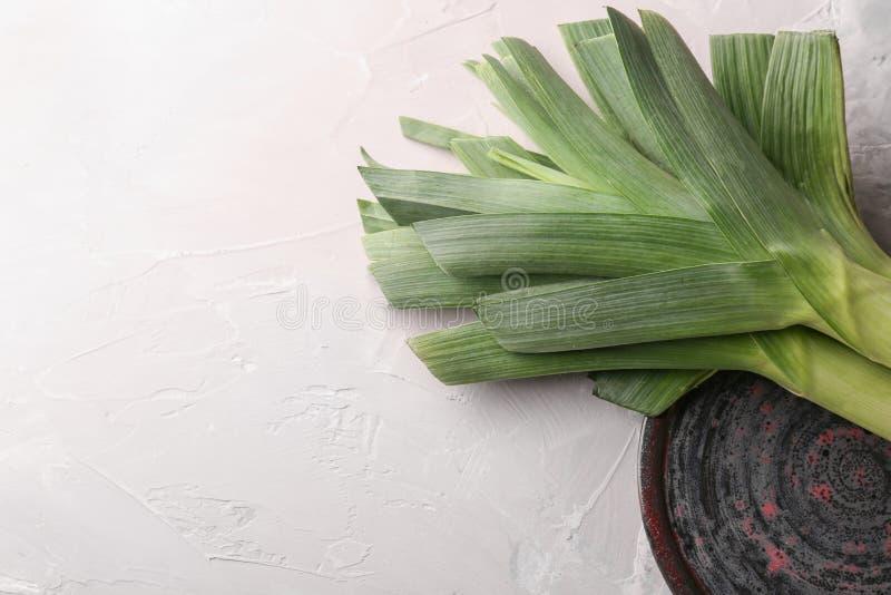 Плита с сырцовыми лук-пореями на светлой таблице стоковые фото