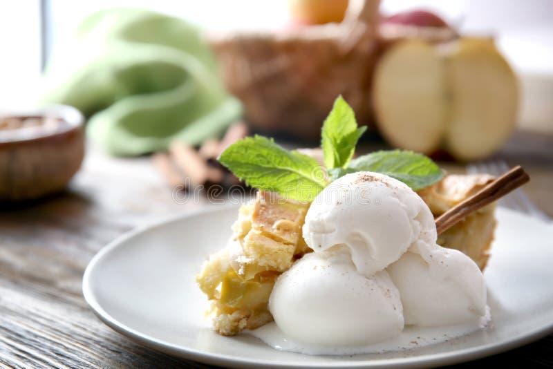 Плита с частью очень вкусного яблочного пирога и мороженого на деревянном столе, крупном плане стоковые изображения
