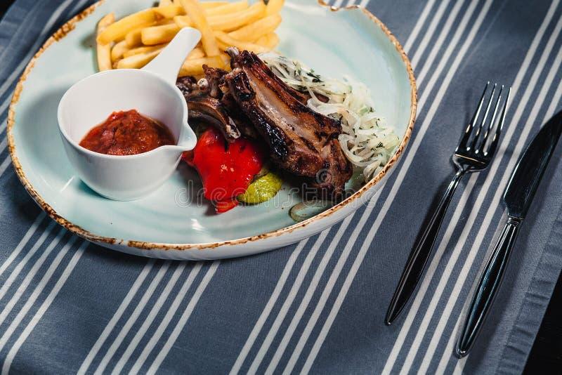 Плита с шкафом овечки, зажаренных фраев овощей, смычка, соуса и француза Clouse вверх стоковая фотография rf