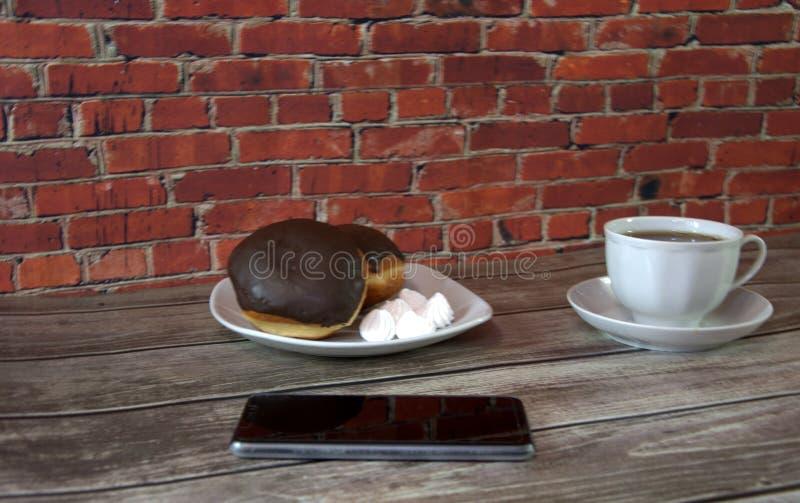Плита с donuts и зефирами, чашкой чаю и ложью смартфона на деревянном столе против красной кирпичной стены : стоковое фото