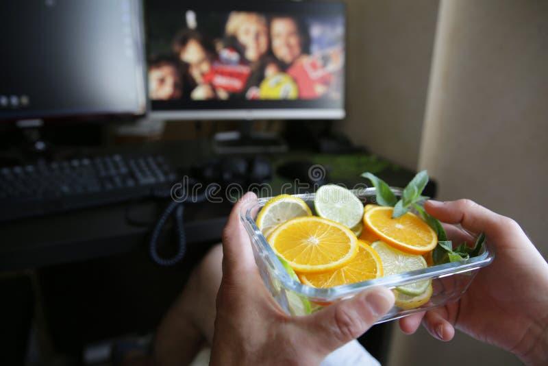 Плита цитрусовых фруктов в их руках против фона мониторов и клавиатуры компьютера E стоковые фото
