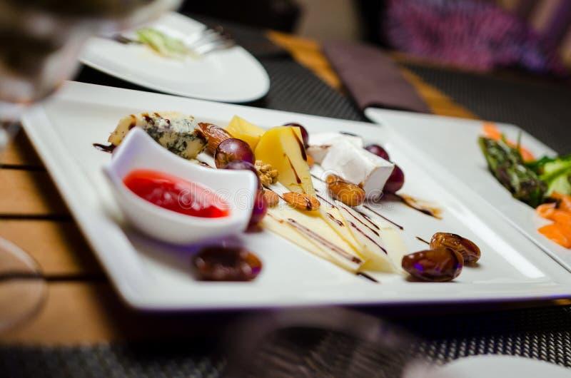 Плиты сыра служили с виноградинами, вареньем, смоквами, шутихами и гайками на деревянной предпосылке, концом вверх по взгляду стоковые фотографии rf