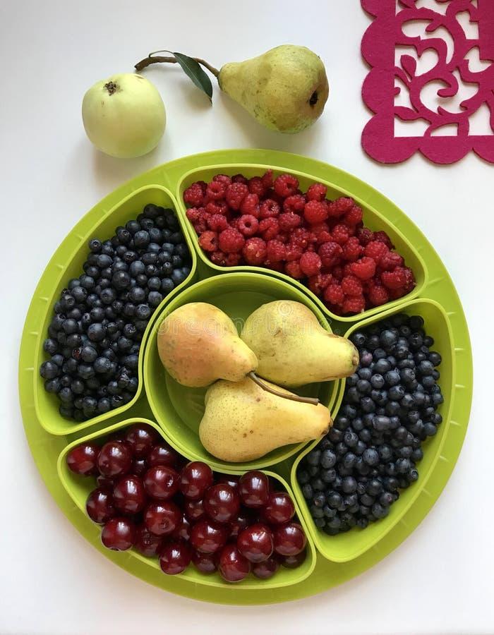 Плодоовощи и ягоды лежат в контейнерах на круглом подносе стоковое фото