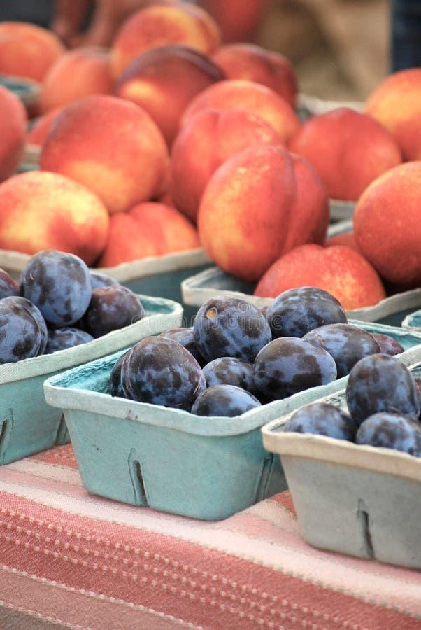 Плодоовощ лета - сливы и персики на рынке фермеров стоковое фото rf