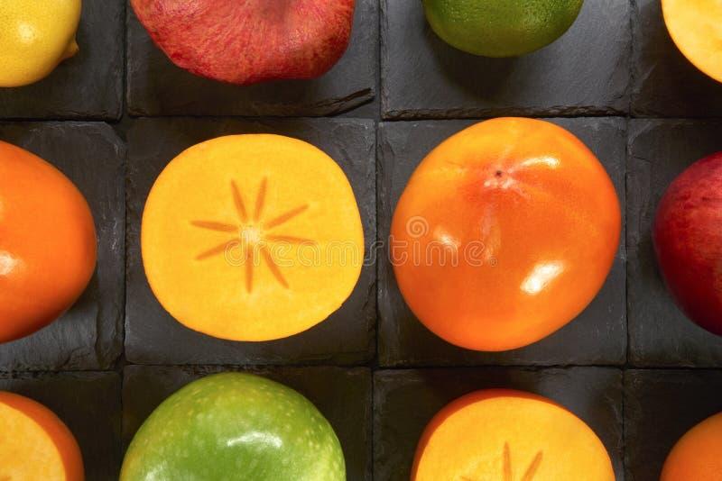 Плодоовощ Kaki среди другого приносить на черных квадратах сделанных камня сланца стоковые изображения