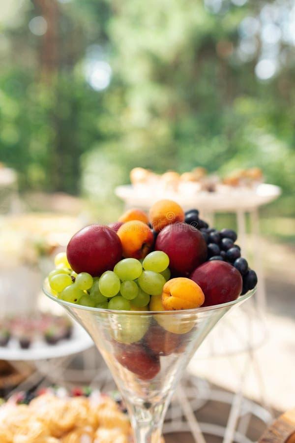 Плоды в стекле Оформление свадьбы Свадьба лета в древесине виноградины, абрикосы стоковое изображение
