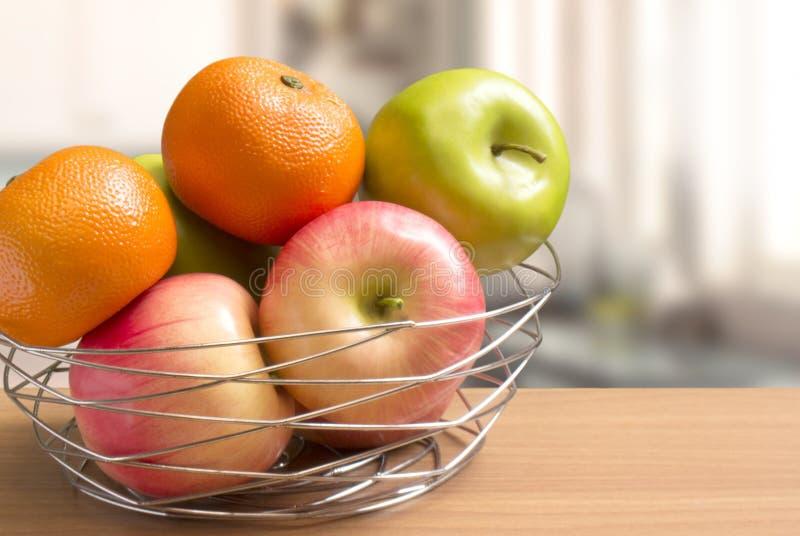 Плоды конца-вверх как яблоки и апельсины в декоративно корзине провода положенной на встречную таблицу, кухню запачкали предпосыл стоковое изображение