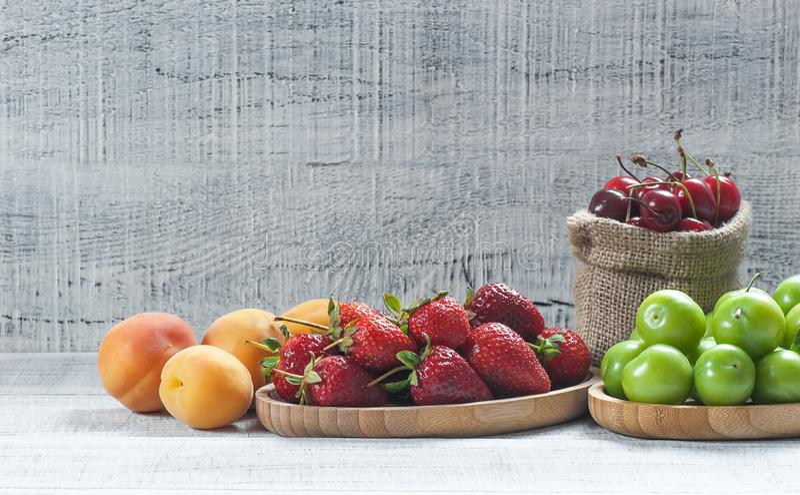 Плоды лета, зеленая слива, красная вишня, клубника, абрикос на белой деревянной предпосылке стоковое фото rf
