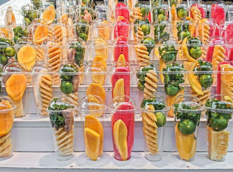 Плоды смешивания в пластиковом стекле на деревянных полках стоковые изображения