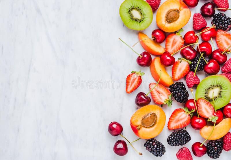 Плоды, ягоды на белом мраморном космосе экземпляра таблицы еда принципиальной схемы здоровая стоковое фото rf