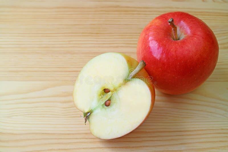 Плод свежего красного яблока весь и свое поперечное сечение на деревянном столе с космосом экземпляра стоковые изображения rf