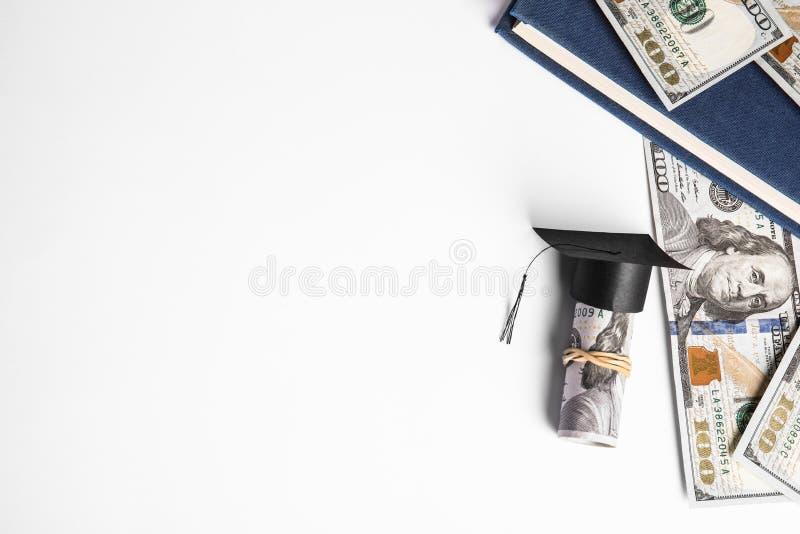Плоская композиция с долларовыми банкнотами и шляпой для выпускного на белом фоне Концепция платы за обучение стоковое фото