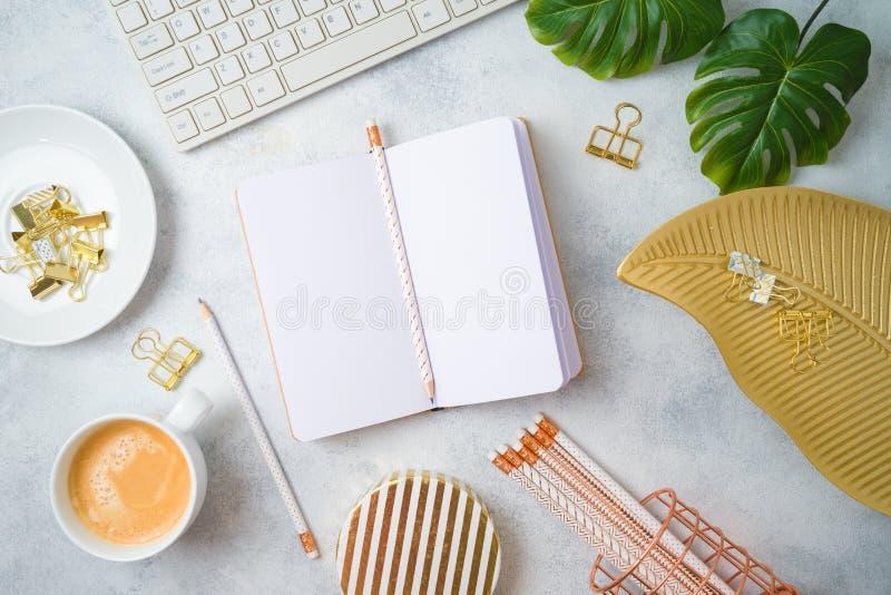 Плоская положенная таблица домашнего офиса женственная с тетрадью, золотыми аксессуарами, клавиатурой компьютера и тропическими л стоковые изображения