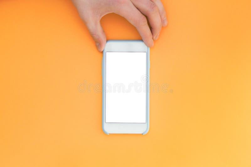 Плоская рука положения с телефоном Рука держит smartphone с белым экраном na górze оранжевой предпосылки стоковые изображения