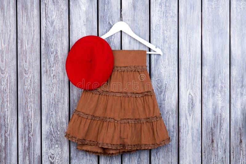 Плоская юбка коричневого цвета положения и красная шляпа на таблице стоковые фото