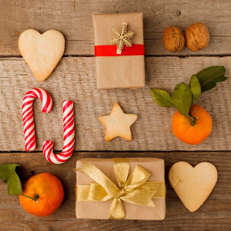 Плоские подарки на рождество положения, творчески в оболочке и украшенных в коробках на винтажной деревянной предпосылке стоковое изображение