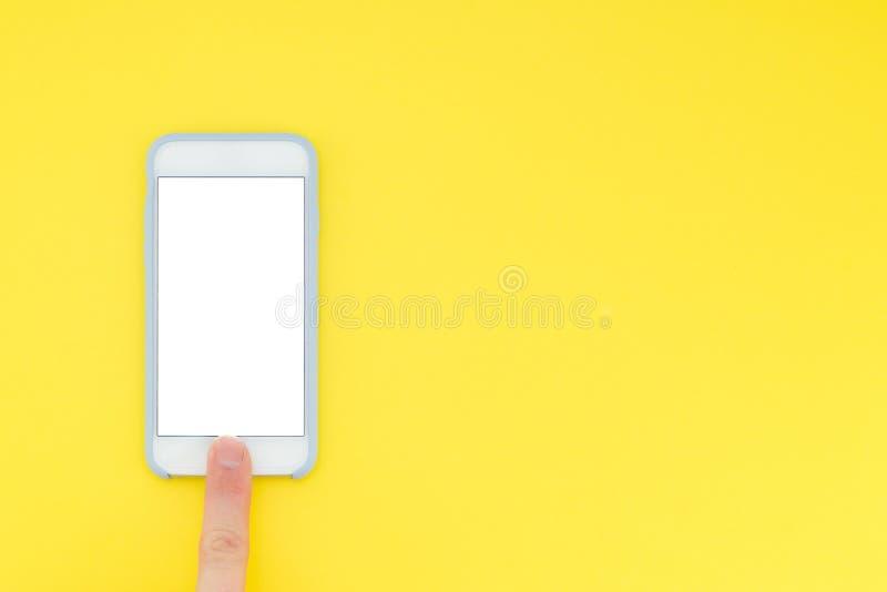 Плоские smartphone и рука положения Взгляд сверху установьте текст Фото Minimalistic smartphone и пальца который открывает его стоковые фото