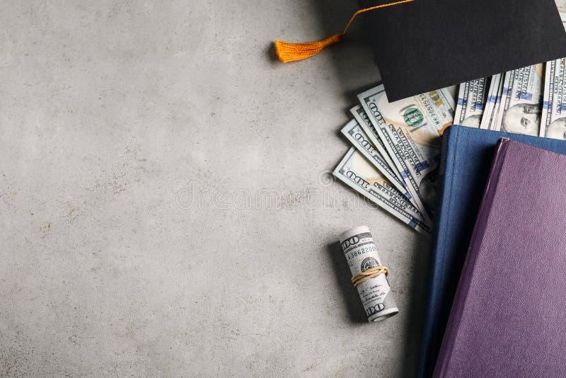 Плоский композиция с долларами и студенческой шляпой на каменном фоне Концепция платы за обучение стоковое фото rf