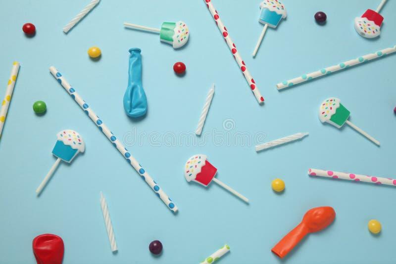Плоский положенный день рождения childs, голубая картина предпосылки Сладкие конфеты, яркий воздушный шар, праздничные свечи, пир стоковые фото