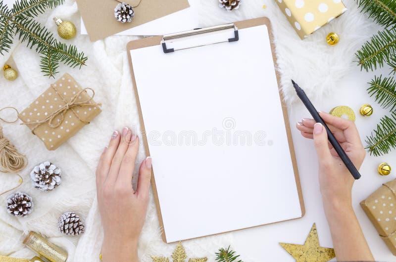 Плоский положенный модель-макет доски сзажимом для бумаги рождества Руки женщины держат черную ручку щетки Пустая насмешка доски  стоковые изображения