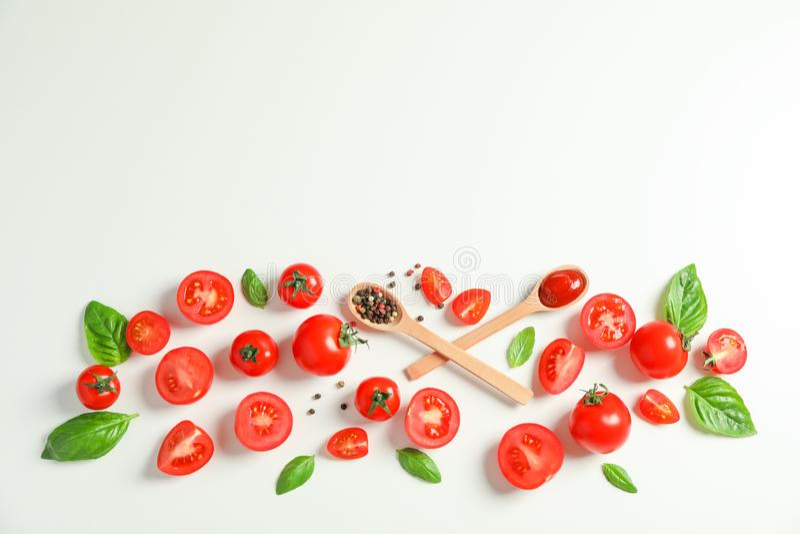 Плоский положенный состав со свежими томатами, перцем, базиликом и деревянными ложками на белой предпосылке, космосе для текста стоковая фотография