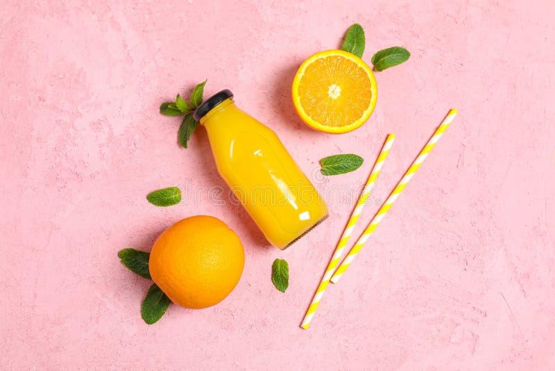 Плоский положенный состав с апельсинами, tubules, апельсиновым соком в бутылке и мятой на предпосылке цвета, космосе для текста стоковое фото rf