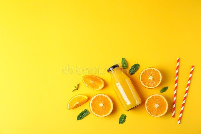 Плоский положенный состав с апельсинами, tubules и апельсиновым соком в бутылке, космосе для текста стоковые фото