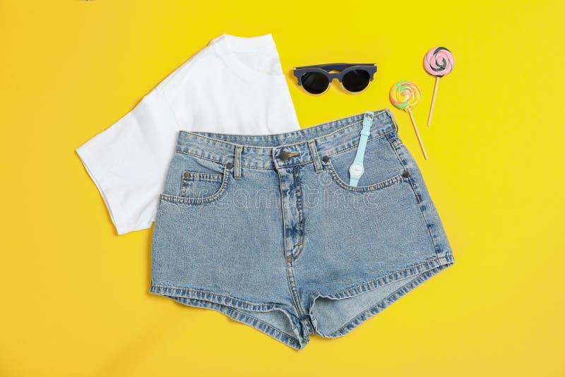Плоский положенный состав с: одежды женщин и аксессуары, тросточки конфеты на желтой предпосылке стоковые изображения rf