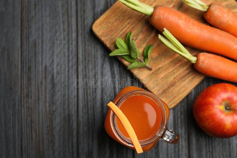 Плоский положенный состав с опарником каменщика напитка моркови на деревянном столе стоковые фотографии rf